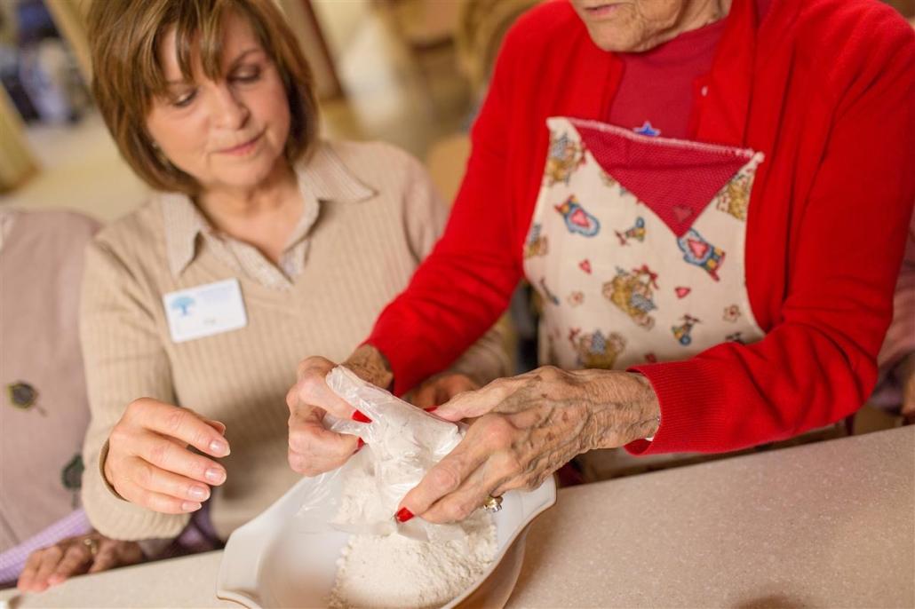 senior woman emptying flour into bowl