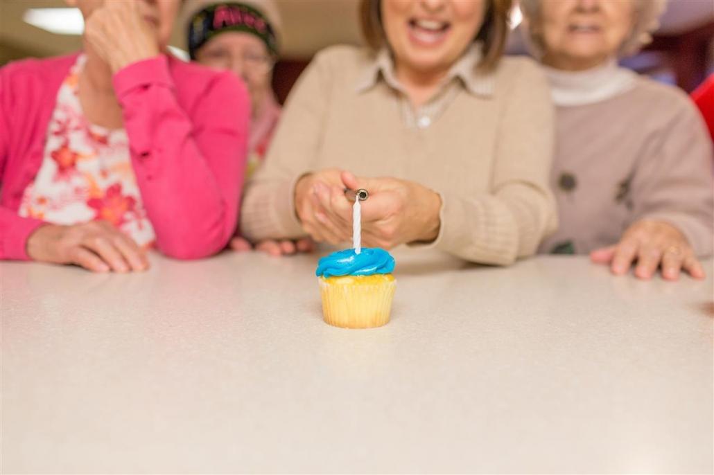 woman lighting candle on cupcake
