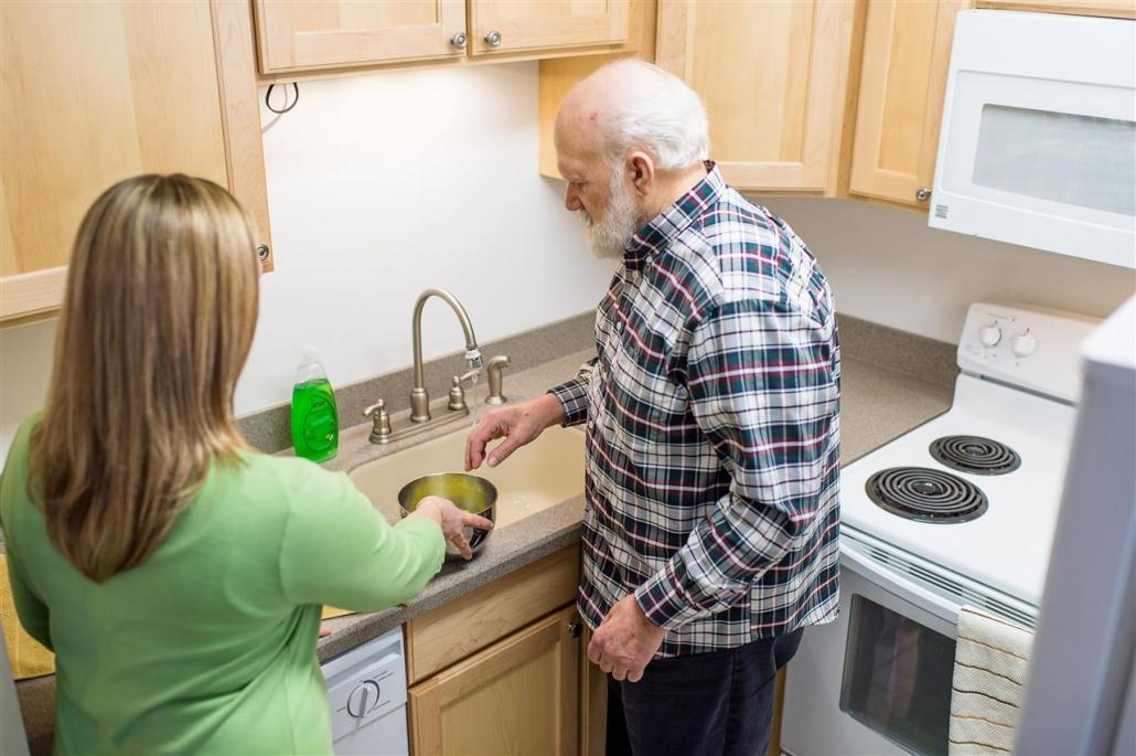 caregiver helping man wash dishes